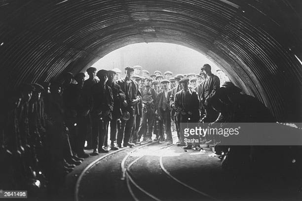 Coal miners standing at the pit head of Tilmanstone colliery Kent The picture was taken using a 'Sashalite' a safe photographic flash developed by...