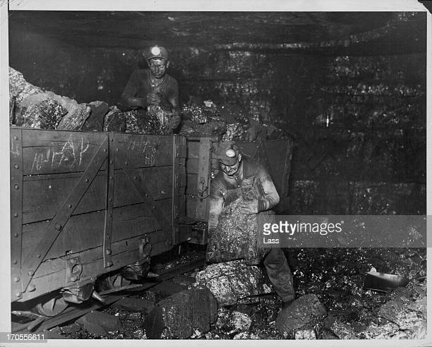 Coal miners under ground carrying out anthracite loading huge lumps are cleared for impurities