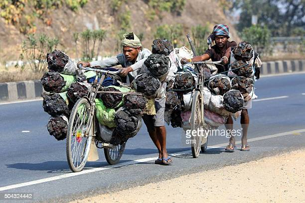 Coal pickers push their bicycles laden with coal collected illegally along the HazaribaghRanchi highway in the Ramgarh district of eastern Jharkhand...