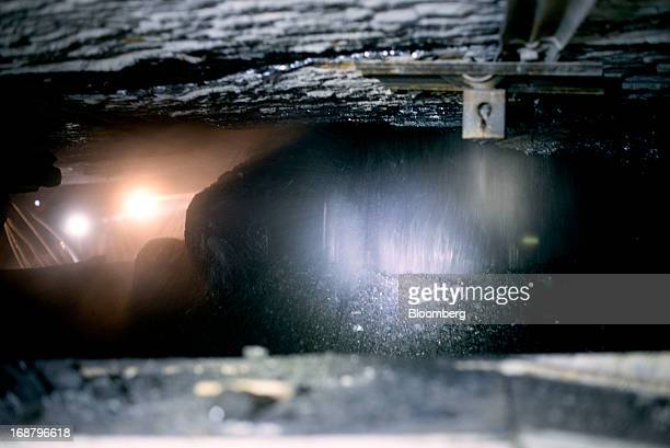 Coal runs along a conveyor belt after being scraped off the wall by a shearer during longwall mining operations at the Consol Energy Bailey Mine in...