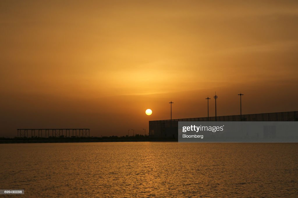 A coal storage area stands at the Sahiwal coal power plant owned by China`s stateowned Huaneng Shandong Rui Group at sunset in Sahiwal Punjab...
