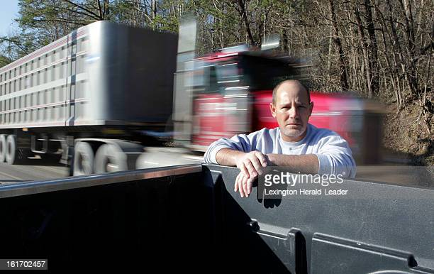 A coal truck passes as Frank Dixon stands at the entrance to the Cumberland River Coal Co Blue Ridge Complex mine where he used to work in Letcher...