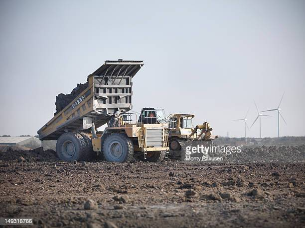 Coal trucks reinstating the land at an opencast coal mine