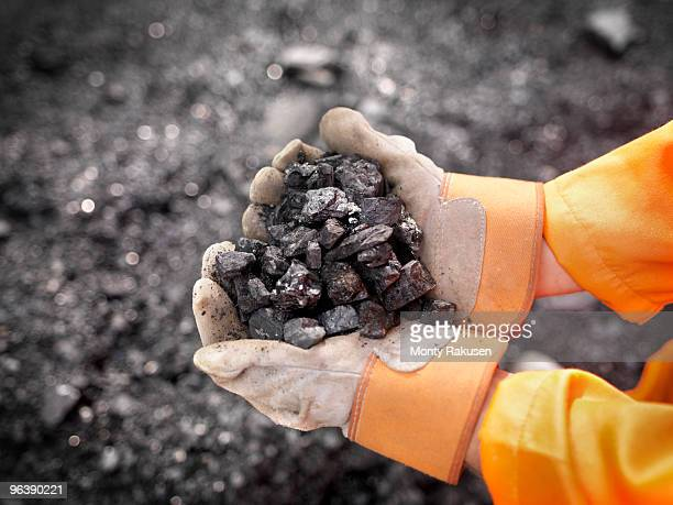 coal worker with handful of coal - coal mining stock photos and pictures