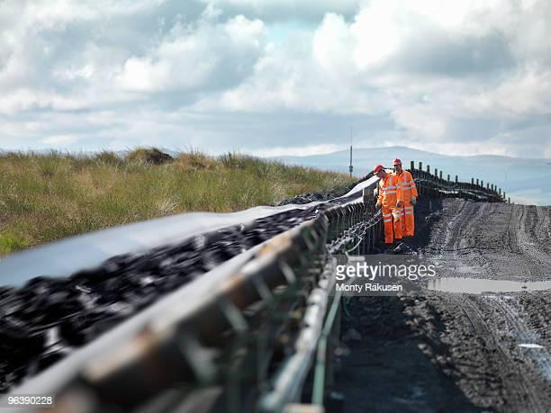 coal workers inspecting conveyor belt - monty rakusen stock photos and pictures