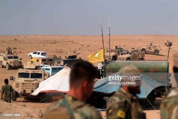 Coalition forces and members of the Syrian Democratic Forces gather at their operation room near the village of Susah in the eastern province of Deir...