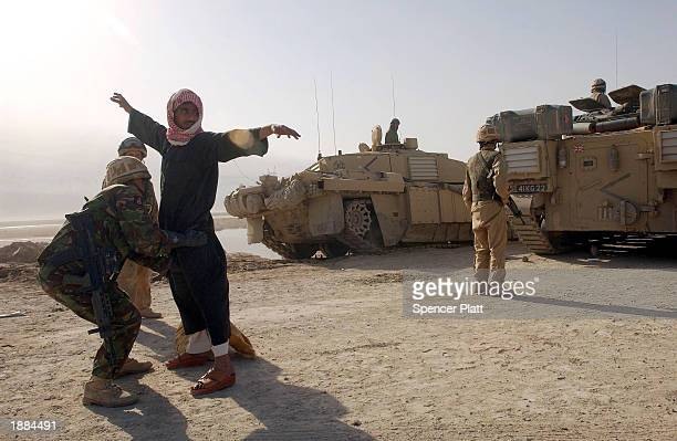 Coalition forces search a man at a checkpoint near the entrance to the besieged city of Basra March 29 2003 in Iraq Baath Party loyalists have taken...