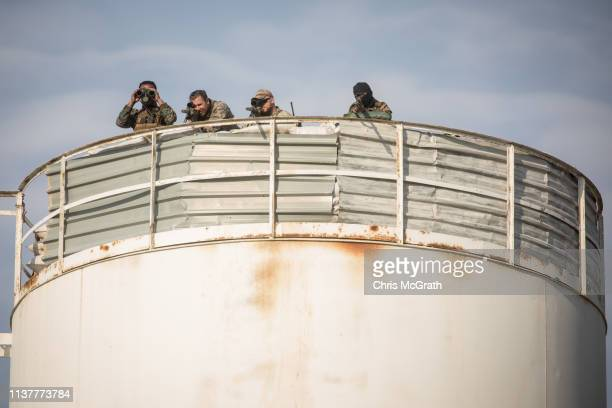 Coalition snipers keep lookout over the SDF victory ceremony announcing the defeat of ISIL in Baghouz held at Omer Oil Field on March 23, 2019 in...