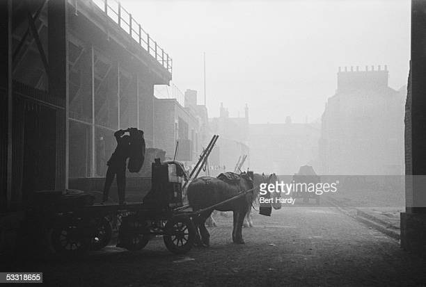 A coalman unloading sacks from a horsedrawn cart underneath the railway arches in the Elephant and Castle area of London 8th January 1949 Original...