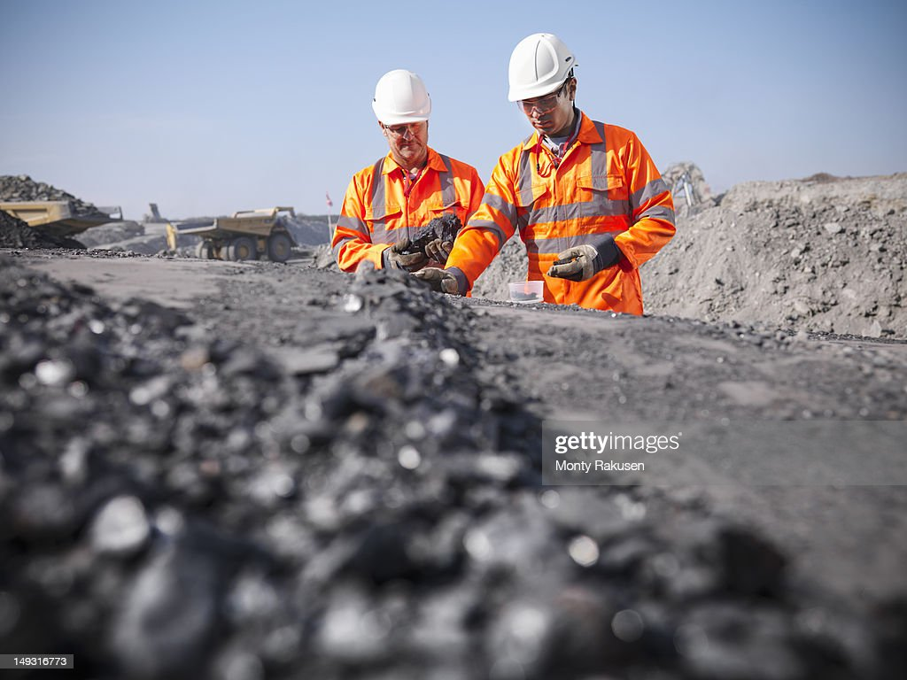 Coalminers inspecting coal in an opencast colamine : Stock Photo