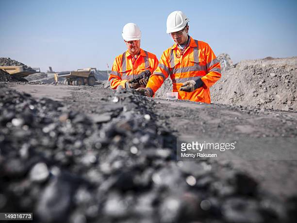 Coalminers inspecting coal in an opencast colamine