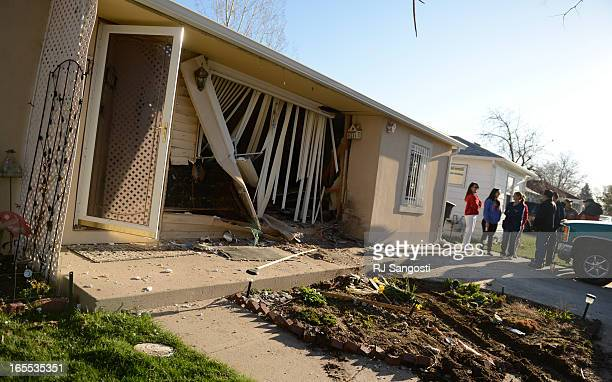 Family and friends wait for Denver Fire to shore up the walls in a home where a car crash into a house at the 5100 block of Gill Place in Denver...
