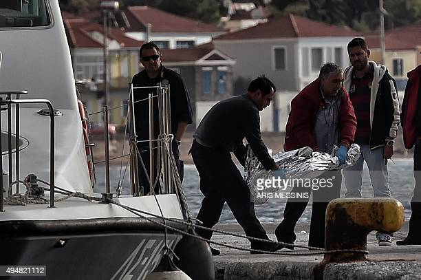 A coast guard and a funeral service employee carry the dead body of a child on the Greek island of Lesbos on October 29 2015 At least five migrants...