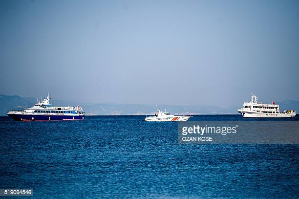 A coast guard boat escorts two small Turkish ferries carrying migrants who are deported to Turkey on April 4 2016 as they arrives at the port of...