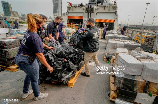 US Coast Guard crewmen DEA agents and other law enforcement officials prepare to offload bundles of drugs aboard the Coast Guard Cutter Bertholf on...