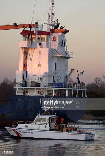 S Coast Guard cutter patrols the Savannah River while the USNS Mendonca is loaded with a cargo of Army vehicles and containers January 14 2003 at the...