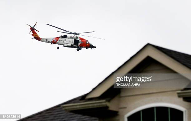 Coast Guard helicopter flies over Autumn Lake a subdivision in Pearland Texas looking for flood victims on August 29 2017 Houston police officer...