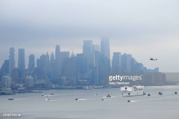 Coast Guard helicopter flies over the USNS Comfort hospital ship as it sails in the Hudson River in front of the skyline of lower Manhattan after...