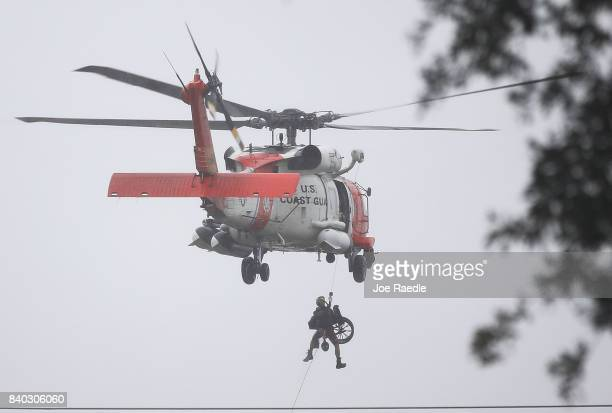 Coast Guard helicopter hoists a wheel chair on board after lifting a person to safety from the area that was inundated with flooding from Hurricane...