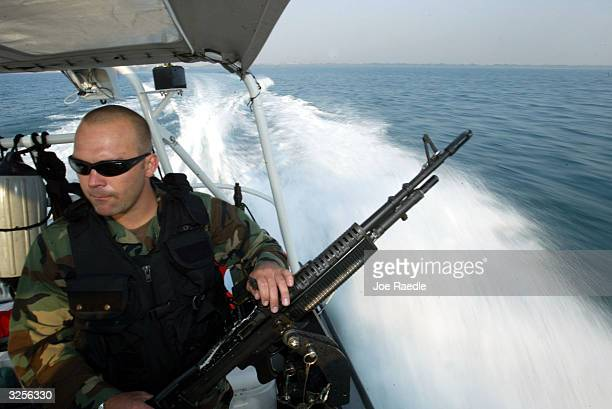 S Coast Guard Jeremy Cummings mans his M60 machine gun on a patrol boat that is part of Joint Task Force operations where detainees from the...