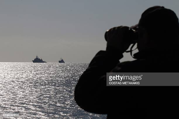 A coast guard looks at a navy ship towing the Kiribatiflagged ferry Baris carrying some 700 migrants off the Cretan port of Ierapetra on November 27...