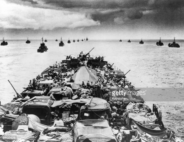 Coast Guard manned LST closely packed with motorised fighting equipment leads in a flotilla of LCTs off New Guinea Antiaircraft guns are at the ready...