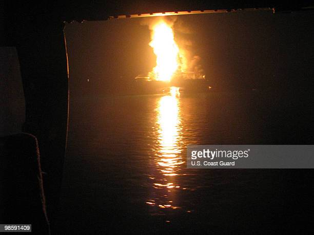Coast Guard MH65C dolphin rescue helicopter and crew document the fire aboard the mobile offshore drilling unit Deepwater Horizon while searching for...