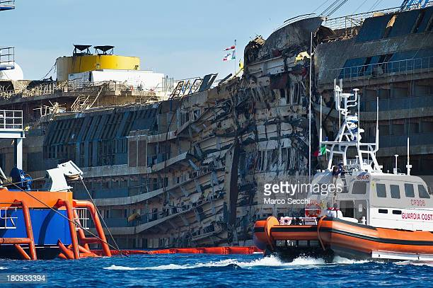 Coast Guard patrols in front of the severely damaged right side of the Costa Concordia cruise ship on September 18 2013 in Isola del Giglio Italy The...