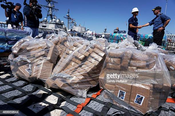 Coast Guard personel stand aboard the USS Boutwell while officials unload bails of cocaine caught at sea while on deployment on April 16 2015 at...