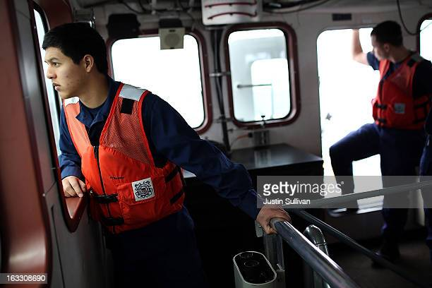 S Coast Guard petty officer Ervin Mantilla of the US Coast Guard Cutter Hawksbill looks out a window as he investigates a fishing vessel while on...