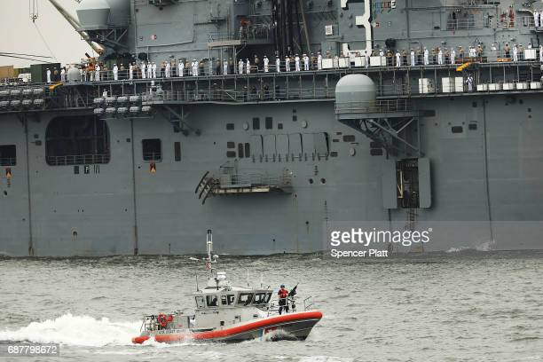 Coast Guard security boat keeps guard in New York Harbor as boats move past the Statue of Liberty on the opening day of Fleet Week on May 24 2017 in...