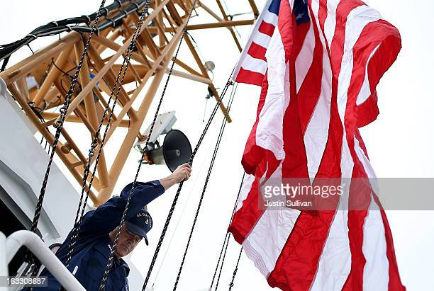 S Coast Guard senior chief petty officer Louis Coleman raises flags aboard the US Coast Guard Cutter Hawksbill before going out on patrol on March 7...