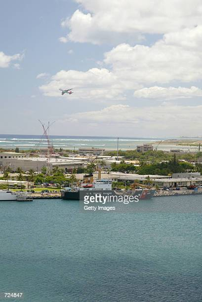 A US Coast Guard ship is docked June 13 2002 in Honolulu Harbor Hawaii as an airliner takes off from the Honolulu Airport The Coast Guard has warned...