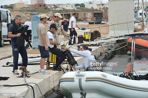 Coast guard's divers prepare their equipments in the Lampedusa harbour on October 6 2013 before operations to recover bodies from the shipwreck that...