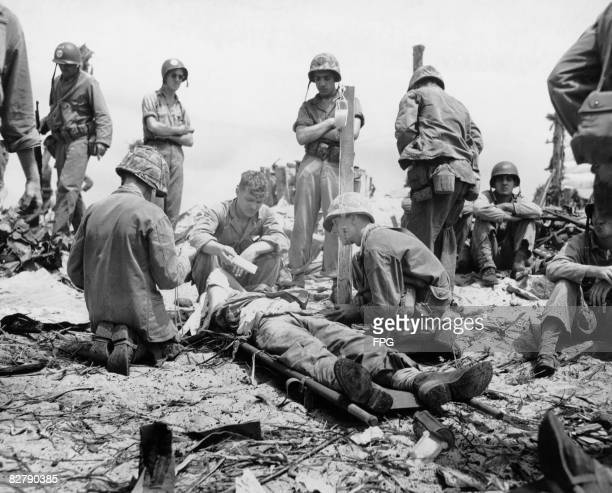 US Coast Guardsmen and Marines give blood plasma to a casualty of the fighting at the Battle of Eniwetok an atoll in the Marshall Islands 17th 23rd...