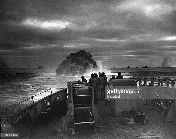 Coast Guardsmen on the deck of the U.S. Coast Guard Cutter Spencer watch the explosion of a depth charge which blasted a Nazi U-boats's hope of...