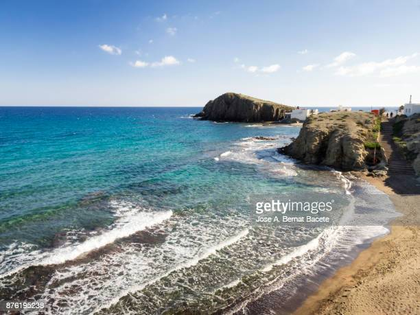 Coast line with cliffs and beaches with a small fishing village by the sea. Cabo de Gata - Nijar Natural Park, Beach of the white crag and the people, Isleta of the Moor, Biosphere Reserve, Almeria,  Andalusia, Spain.