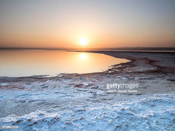Coast of a salty lake with formations of salt, during a putting Sun with reflections in the water of orange color