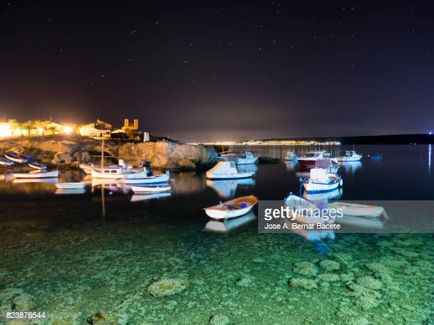 coast of the island of tabarca with the ships of fishing tied in the night and landscape of the town of tabarca island in the mediterranean sea, spain. - alicante stock pictures, royalty-free photos & images