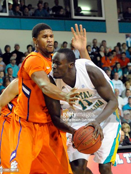 Coastal Carolina's El Hadji Ndieguene drives against Clemson's Devin Booker left during the first half at The HTC Center in Conway South Carolina on...