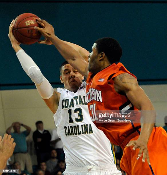 Coastal Carolina's Michael Enanga battles Clemson's Devin Booker for a rebound during the second half at The HTC Center in Conway South Carolina on...
