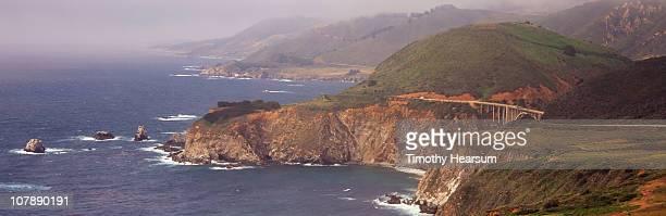 coastal cliffs and bridge in fog - timothy hearsum stock-fotos und bilder