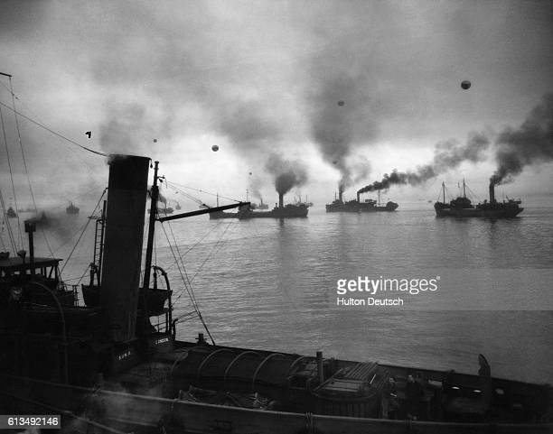 Coastal convoy prepare to leave a British port at dawn guarded by escord ships, an RAF umbrella and barrage balloons which can be seen through the...