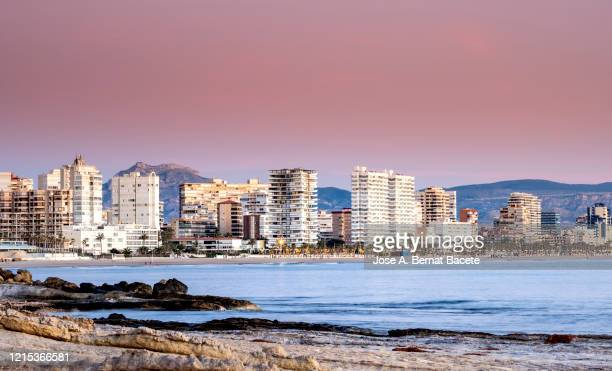 coastal landscape at sunrise with the city of san juan de alicante, valencian community, spain. - alicante stock pictures, royalty-free photos & images