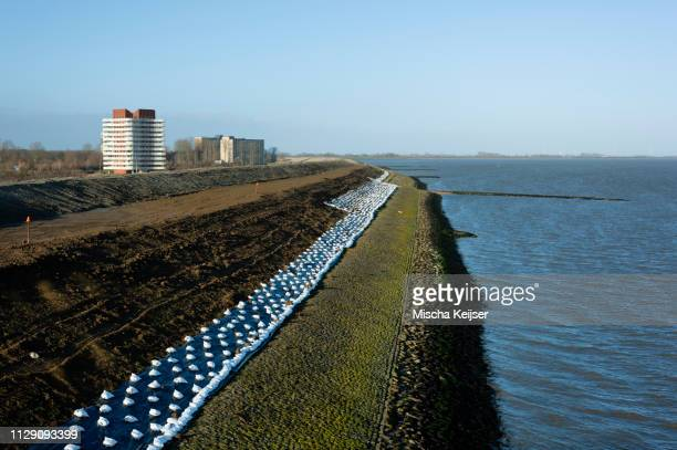 coastal landscape with reinforced sea dyke to withstand future storms, netherlands - levee stock pictures, royalty-free photos & images