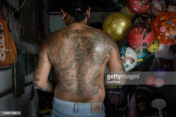 Coastal park worker with traditional tattoos on his back at his working place in Denpasar Bali Indonesia in November 2018