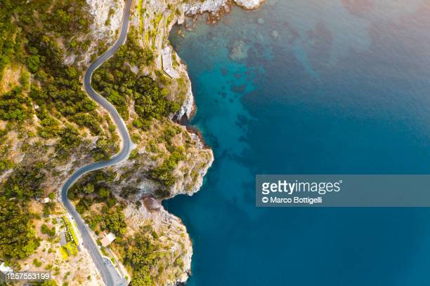 coastal road and deep blue sea along the amalfi coast, italy - curve stock pictures, royalty-free photos & images