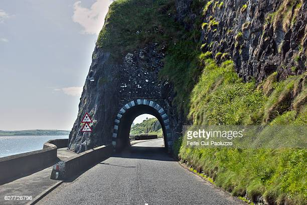 coastal road and tunnel at larne in county antrim of northern ireland - county antrim stock pictures, royalty-free photos & images