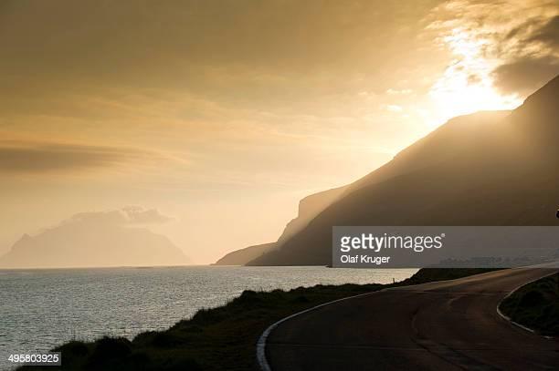 Coastal road, sea and clouds, evening mood, backlighting, Mykines Island at the rear, Mykines, Faroe Islands, Denmark