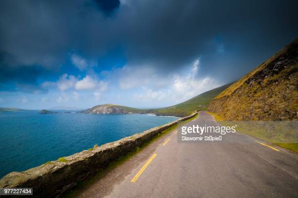 coastal road under moody sky, slea head, ireland - ring of kerry stock photos and pictures